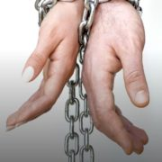 Two pairs of hands bound together with a chain