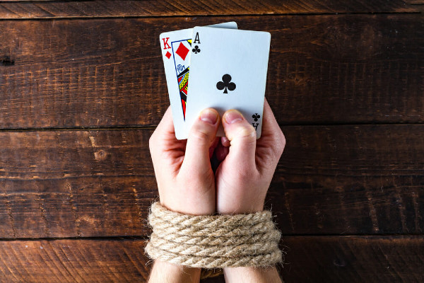Two caucasian hands bound by rope on a wooden table holding a king of diamonds and an ace of spades #gambling addiction