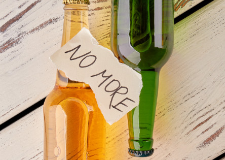 """one green bottle facing downwards, one bottle filled with yellow liquid facing upwards. /the bottles are side by side. Torn paper note on top of the bottles with pencil writing that says """"No more""""."""
