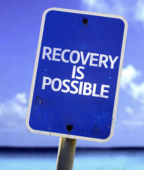 """Blue sign, white writing which reads """"Recovery is Possible"""""""